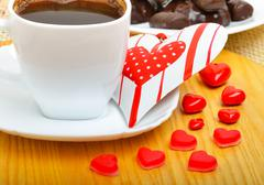 cup of coffee with chocolate sweets a valentine heart on white plate on woode - stock photo