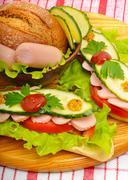 Big appetizing fast food baguette sandwich with lettuce, tomato and frankfurt Stock Photos