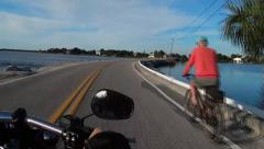 Riding motorcycle on bridge over water, passing man on bicycle Stock Footage