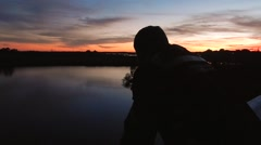 Silhouette of man watching sunset over water Stock Footage