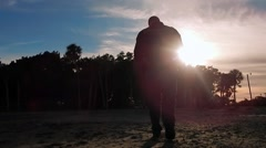 Silhouette of man walking into sunset Stock Footage