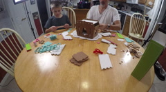 Father and son time lapse of building a ginger bread house Stock Footage