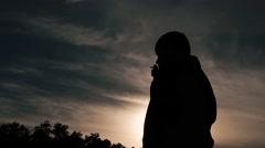 Silhouette of man smoking in sunset Stock Footage