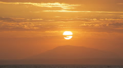 The sun sets directly to the mountain peak. Spectacular sky. Stock Footage