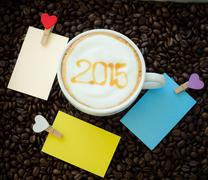A cup of coffee with foam milk art 2015 pattern and clip note Stock Photos