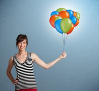 Young woman holding colorful balloons - stock photo