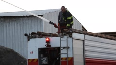 Firefighters spray water on smoking and steaming straw during barn fire. Stock Footage