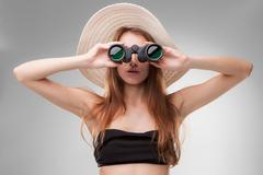Young woman in hat with binoculars Stock Photos