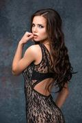 Beautiful young brunette woman with her hair posing in a tracery dress. Studio, Stock Photos
