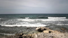 Quiet sea waves clashing at the shore covered in stones Stock Footage