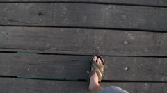 Man feet in sandals walking on a wooden deck on the beach, point of view camera Stock Footage