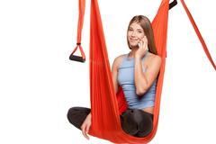 Young woman sitting in hammock for anti-gravity aerial yoga - stock photo