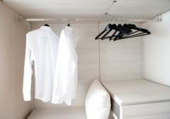 white shirts hanging on built-in cloths racks, with drawers and other accesso - stock photo