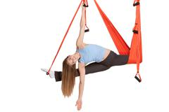 Young woman doing anti-gravity aerial yoga in hammock on a seamless white - stock photo