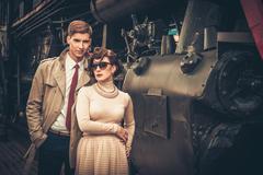 vintage style couple near steam locomotive - stock photo