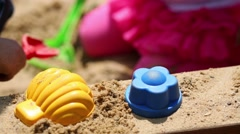 Cute curly children made sand-pie: a shell and flower. Stock Footage