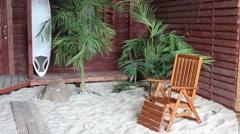 Studio decorated as a beach: armchair, stone, palms, sand Stock Footage