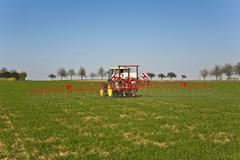 Tractor on field sputtering pest protection Stock Photos