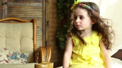 Little girl is sitting in front of fan and looking to the camera. Stock Footage