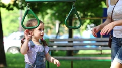 Mother is teaching her daughter how to swing in park. Stock Footage