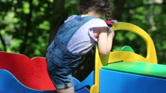 Cute girl in coveralls is playing on a colored car. Stock Footage