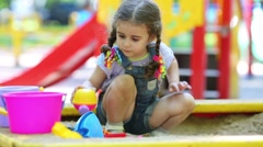 Little curly girl is playing with a scoop in sandbox. Stock Footage