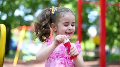 Little girl in pink dress is laughing and playing with bubbles. Stock Footage