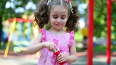 Little girl in pink dress is blowing a soap bubbles. Stock Footage