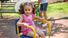 Curly girl in pink dress with a tails is sitting on the carousel. Stock Footage