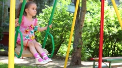 Curly girl in pink dress with a tails is swinging. Stock Footage