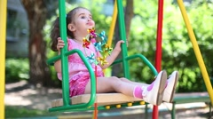 Playful girl in pink dress with a tails is laughing on the swing. Stock Footage