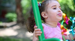 Playful girl in pink dress with a tails is showing her tongue. Stock Footage