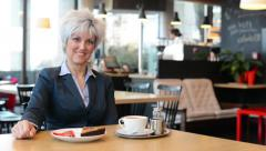 middle aged woman smiles to camera in cafe - coffee and cake - stock footage