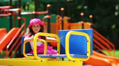 Little cute girl with braids are swinging on carousel. Stock Footage