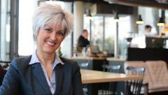 Middle aged woman smiles to camera in cafe - closeup Stock Footage