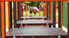 Curly girl in a oink dress is climbing on the playground. - stock footage