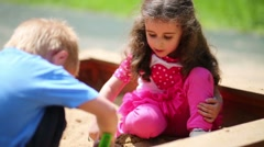 Little boy and girl are playing in the sandbox on playground. Stock Footage