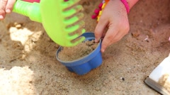 Little curly girl is making a sand-pie in the sandbox. Stock Footage