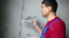 A worker with spatula makes repairs smears on the wall putty. Stock Footage
