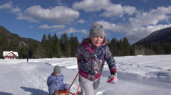 Sister Pulls Younger Brother On Sledge On A Sunny Winter Day Stock Footage