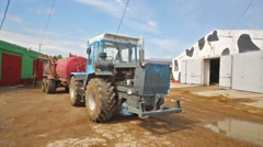 Blue tractor with a red trailer is staying on the farm in farm. Stock Footage