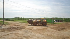 Heavy orange tractor with scoop is going to the farm in farm. Stock Footage
