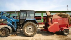 Blue tractor with hay in a trailer on the dairy farm. Stock Footage