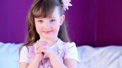 Little girl stand with clasped hands posing in front of camera. Stock Footage