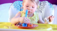 Little girl tries to eats by spoon, sitting on highchair. Stock Footage