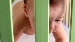 Closeup face of baby boy who crawls in wooden playpen. Stock Footage