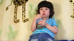 Little boy sits on back of sofa leaning at wall and drinks Stock Footage