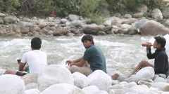 Three friends relaxing by riverside Stock Footage
