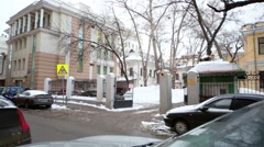 Dirty road with thawed snow, parked cars, open gate to courtyard. Stock Footage