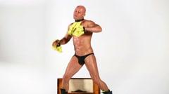 Bald muscular man dances around old radio-gramophone. Stock Footage